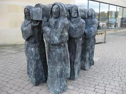 Cuthbert's monks carrying his body to safety by Fenwick Lawson. Original wood carving at Lindisfarne, 2008 bronze at Durham Cathedral